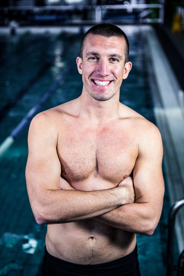 Smiling muscular swimmer with arms crossed stock photo