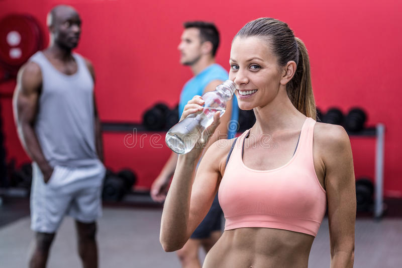 Smiling muscular woman drinking water royalty free stock photography