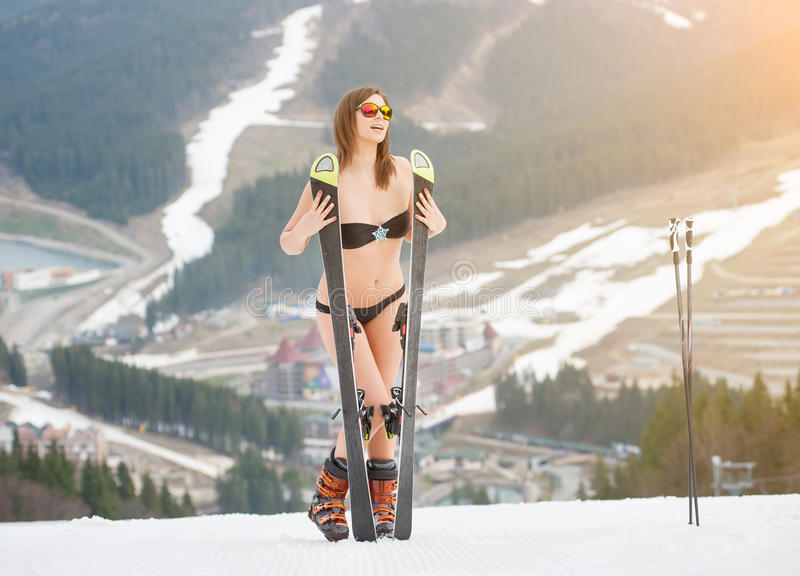 Smiling naked woman is standing on the top of the slope with skis. Wearing swimsuit, boots and sunglasses. Ski resort, mountains, snowy slopes, forests on the stock photography