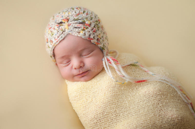 Smiling Newborn Baby Girl Swaddled in Yellow. A portrait of a beautiful, two week old, newborn baby girl wearing a crocheted bonnet. She is smiling and sleeping royalty free stock photography