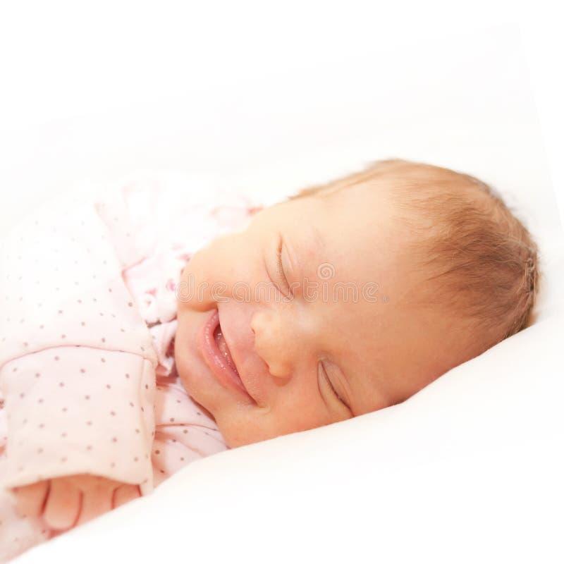 Smiling newborn baby sleeping. Isolated on white stock image