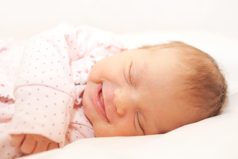 Smiling newborn baby sleeping on white royalty free stock image