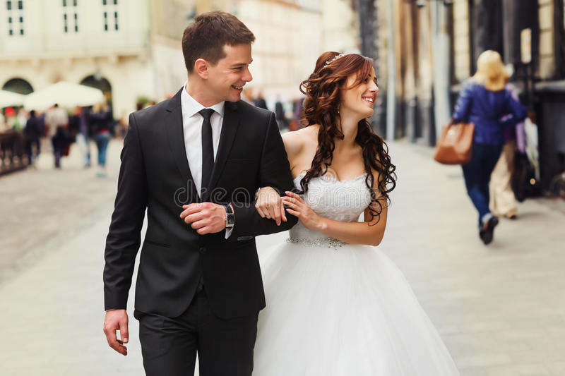 Smiling newlyweds walk along the street looking at old buildings.  stock photo