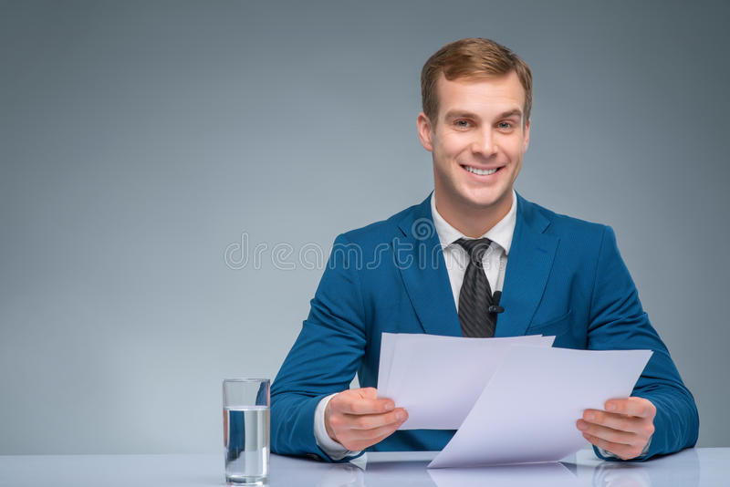 Smiling newscaster during broadcasting. Attractive broadcaster. Handsome newsman is smiling while holding papers for broadcasting royalty free stock photography