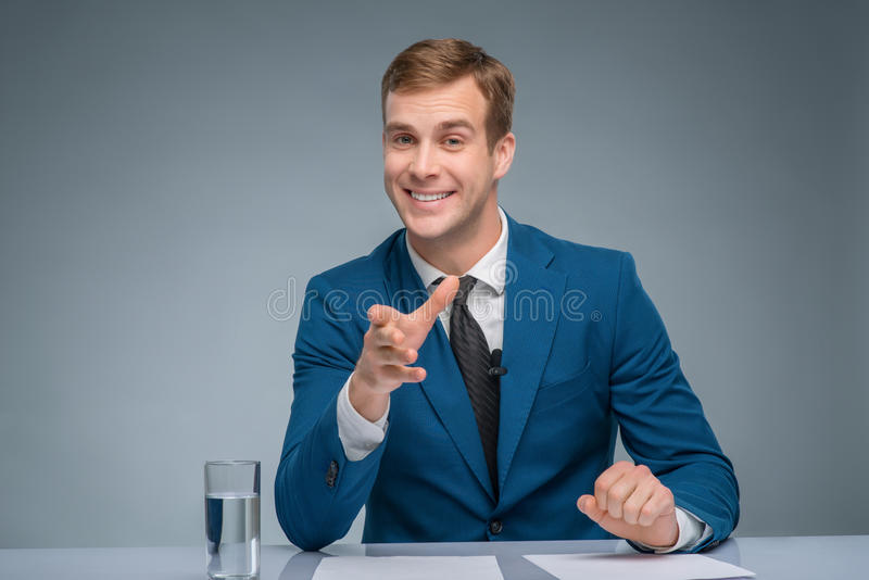 Smiling newscaster during broadcasting. Attractive broadcaster. Handsome newsman is smiling while leading the newscast stock photo