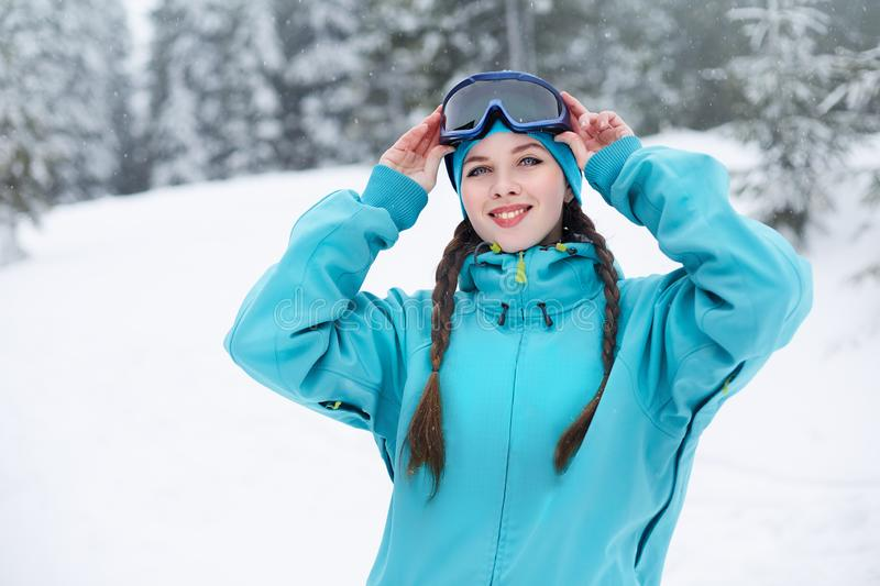 Smiling nordic woman with pigtails puts on protective ski goggles. Snowboarder girl touching mask at ski resort on. Snowfall near forest. Blue eyed elegant stock photos