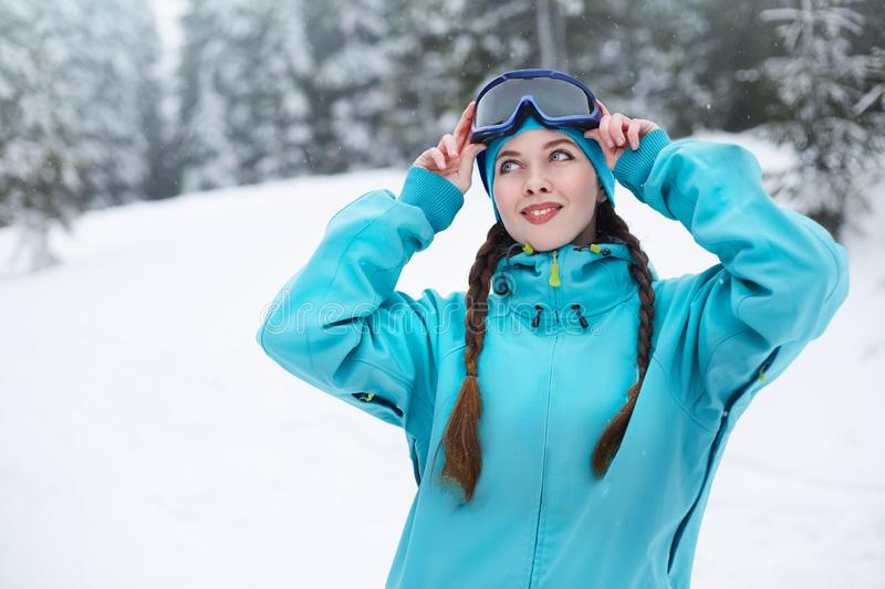 Smiling nordic woman with pigtails puts on protective ski goggles. Snowboarder girl touching mask at ski resort on. Snowfall near forest. Blue eyed elegant royalty free stock image