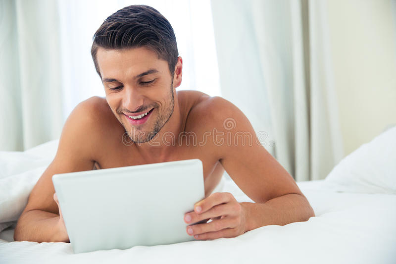 Smiling nude man using tablet computer. Portrait of a smiling nude man using tablet computer in the bed at home stock image