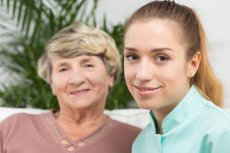 Smiling nurse with an elderly lady stock photography