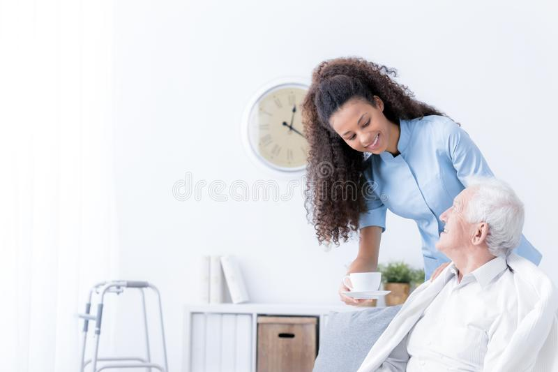 Smiling nurse giving tea to eldery man in the white nursing house. Smiling nurse giving tea to elderly men in the white nursing house concept photo stock photo