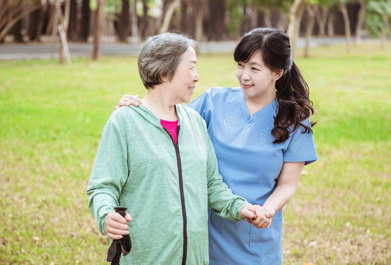 Smiling nurse helping senior woman to walk around the park stock image
