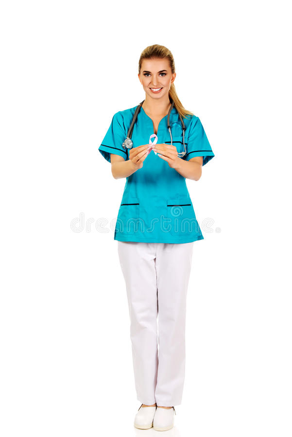 Smiling nurse holding pink breast cancer awareness ribbon stock photo
