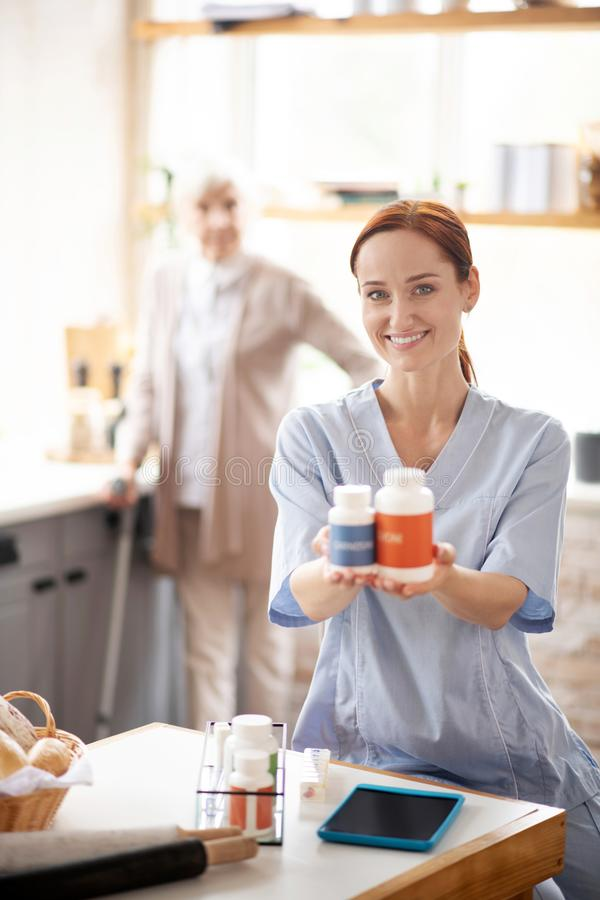 Smiling nurse holding two packs of vitamins. Packs of vitamins. Smiling nurse wearing uniform holding two packs of vitamins royalty free stock images