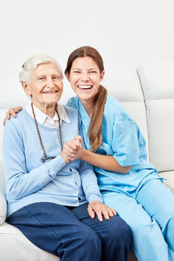 Carer makes home visit to happy senior citizen. Smiling nurse on home care makes home visit to happy senior citizen royalty free stock photos