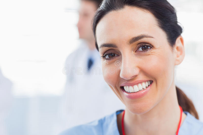 Smiling nurse looking at camera with a doctor behind her. In medical office royalty free stock images