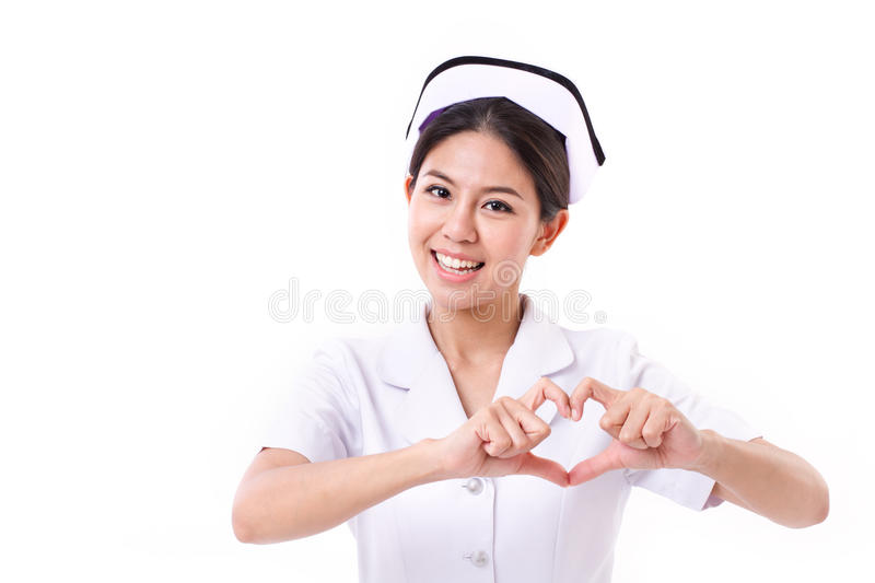 Smiling nurse making heart symbol hand gesture royalty free stock photography