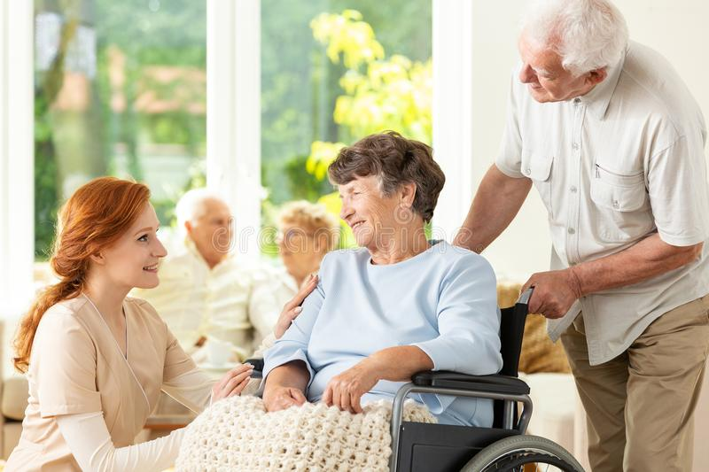 Smiling nurse and senior man supporting paralyzed elderly woman stock images