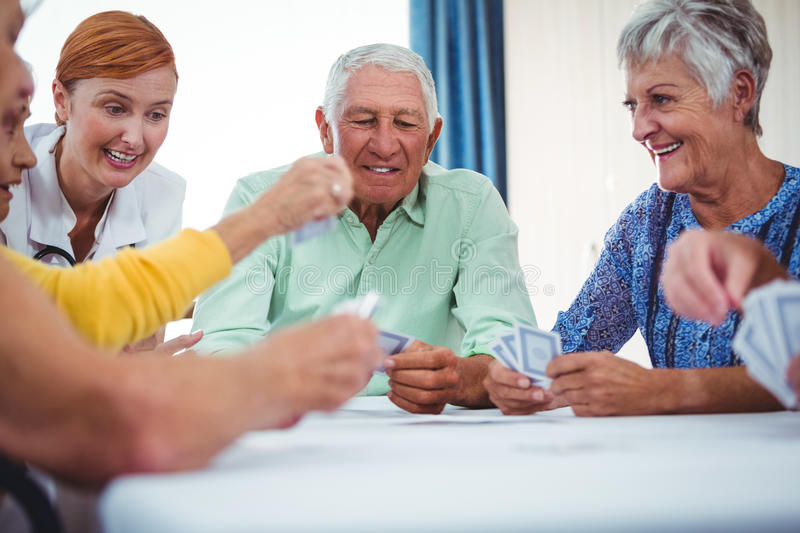 Smiling nurse and seniors people playing cards. In a retirement home stock photos