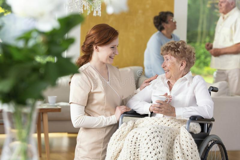 Smiling nurse taking care of happy paralyzed senior woman in the. Smiling nurse taking care of happy paralyzed senior women in the nursing house. Blurred people royalty free stock photo