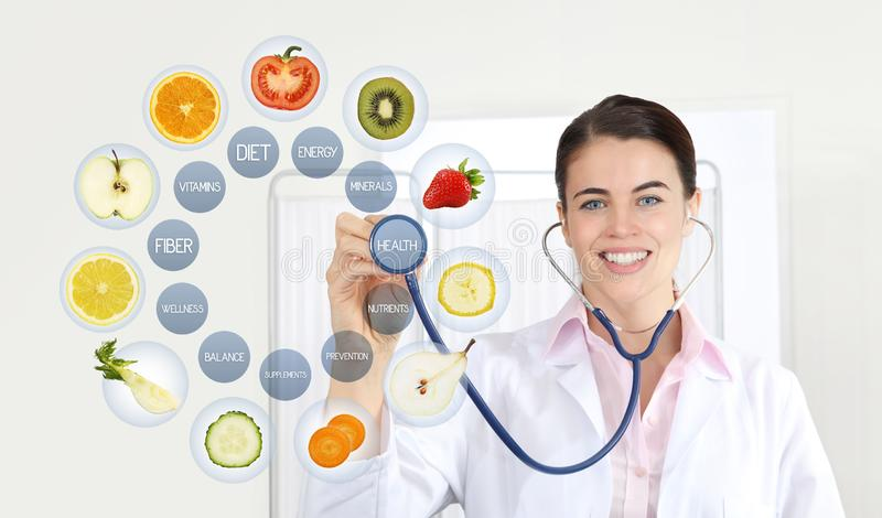 Smiling nutritionist doctor with stethoscope pointing symbols fruits icons and medical texts isolated on white background, healthy royalty free stock images