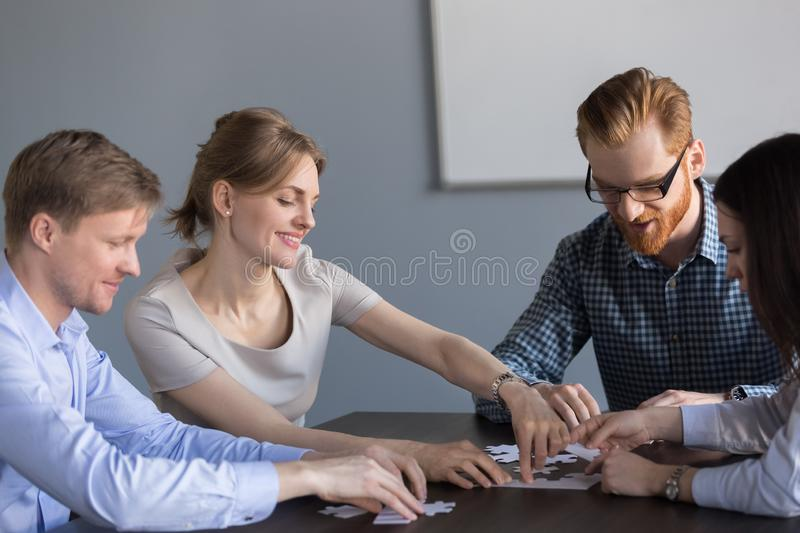 Smiling office team assembling puzzle together at meeting, teamb royalty free stock image