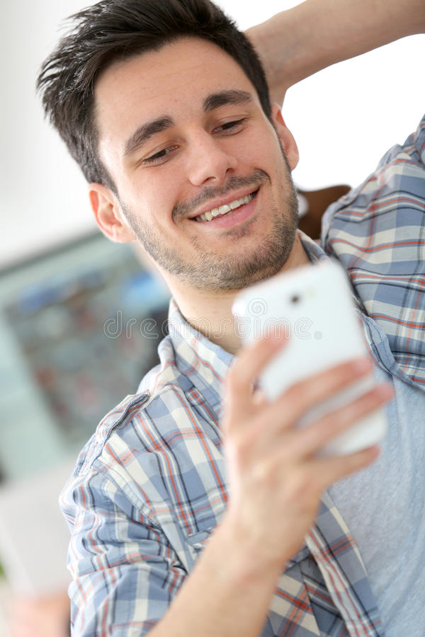 Smiling office worker with smartphone. Office worker using smartphone at work stock images
