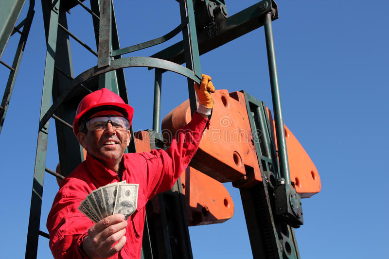 Smiling Oil Worker. Smiling oil industry worker holding dollars bills in his hands on pump jack oil rig stock photography