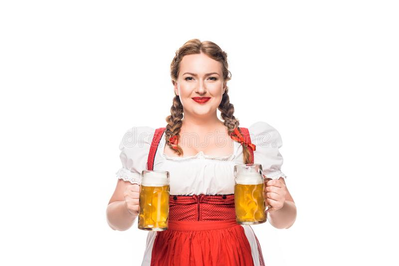 Smiling oktoberfest waitress in traditional german dress with two mugs of light beer. Isolated on white background stock photography