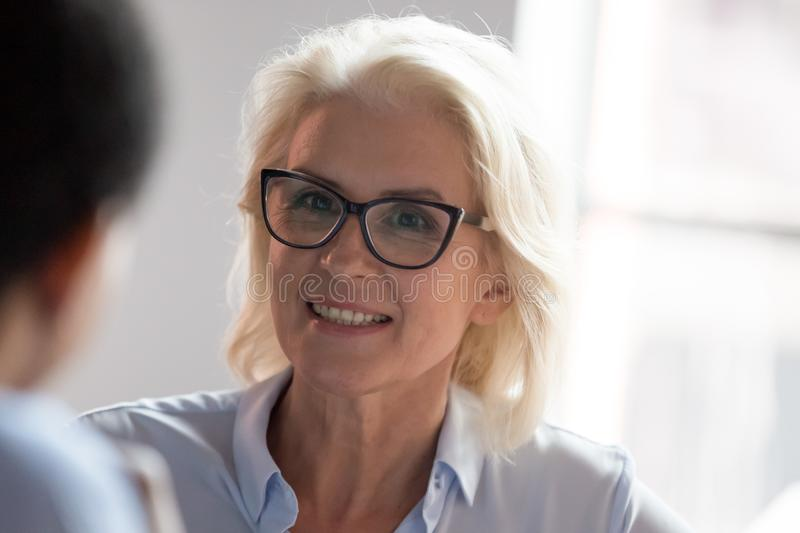Smiling old businesswoman looking at colleague listening client at meeting. Smiling middle aged businesswoman in glasses looking at colleague client at business stock photos