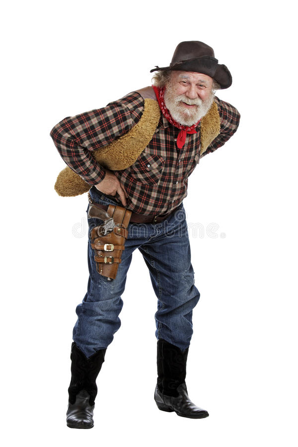 Smiling old cowboy stands leaning forward royalty free stock photo