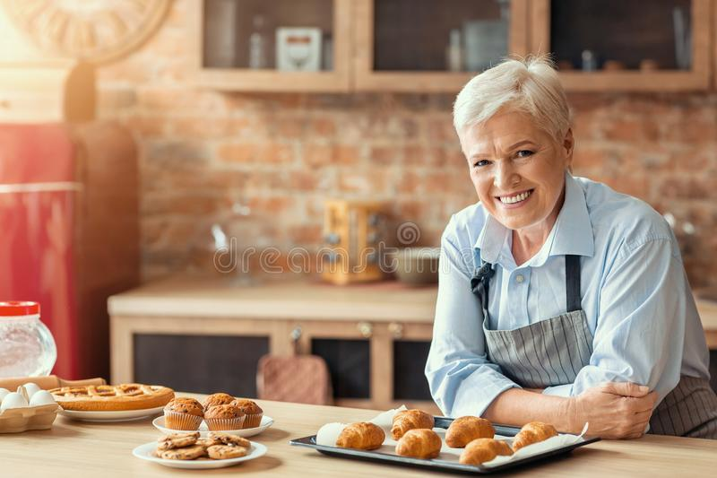 Smiling old lady posing with freshly baked pastry in kitchen. Smiling old lady demonstrating freshly baked pastry in kitchen, empty space stock images
