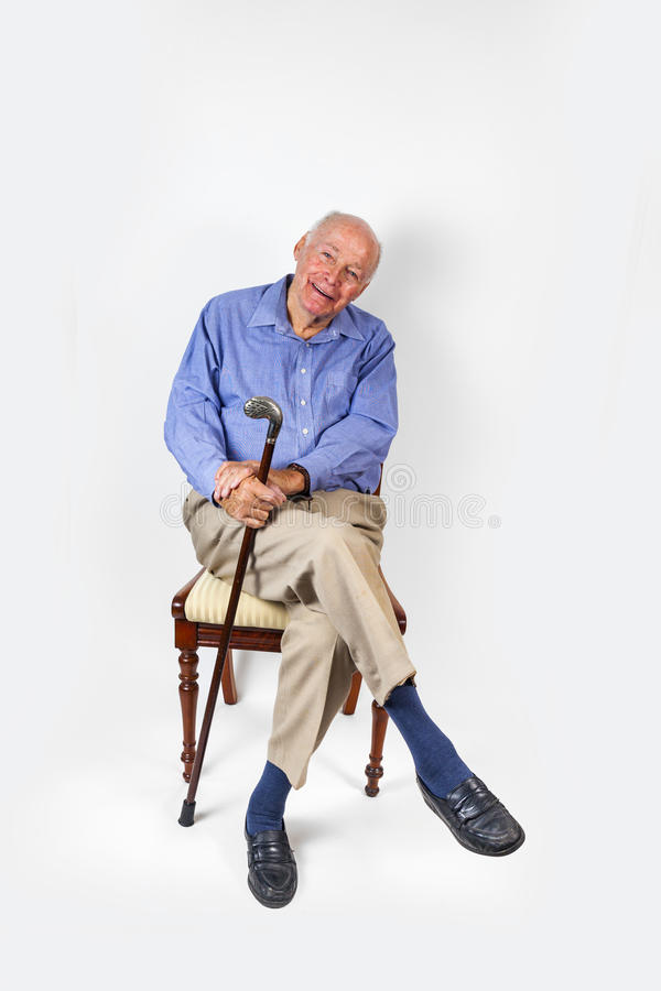 Smiling Old Man Holding A Walking Stick Sits On A Chair Stock Image ...