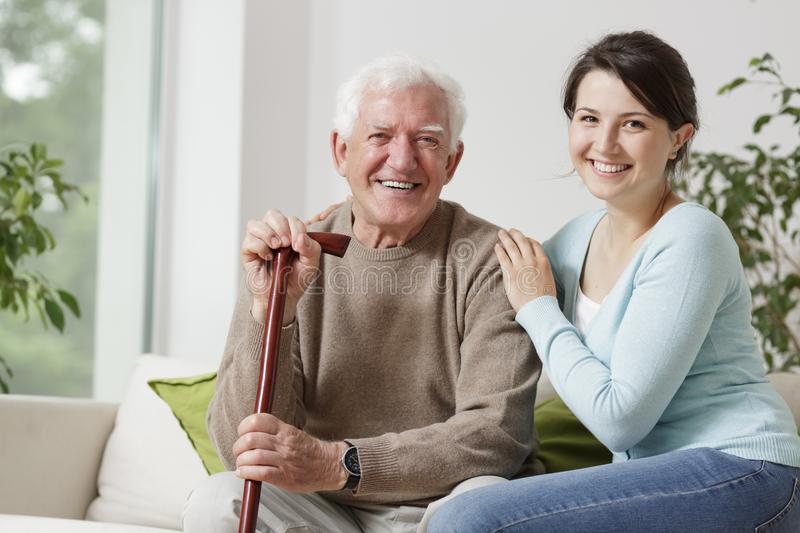 Smiling old man. Smiling old men holding a cane and smiling young woman