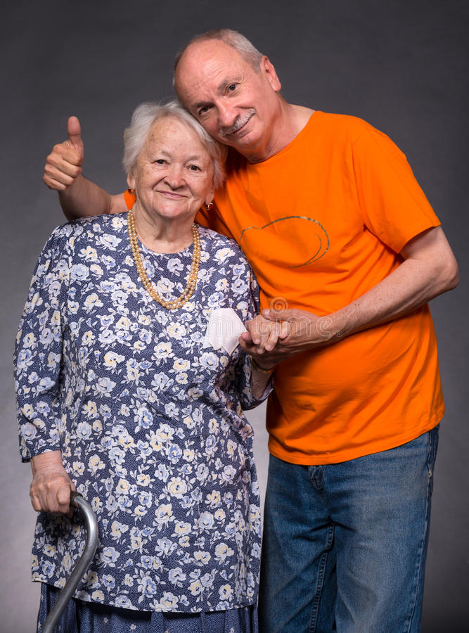 Smiling old mother with elderly son. On a gray background stock photo
