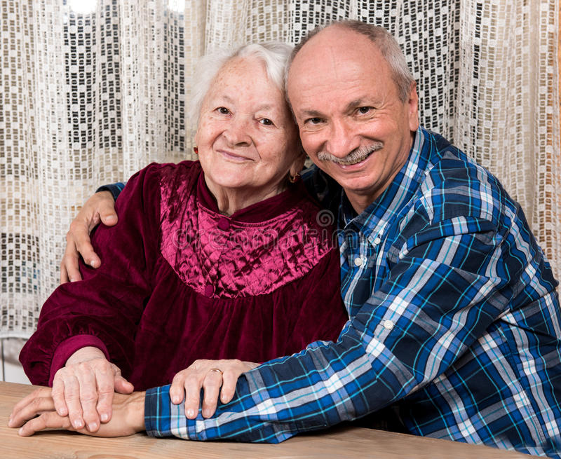 Smiling old mother with elderly son. At home stock images