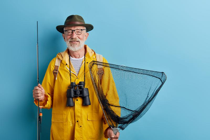 Smiling old senior man being enthusiastic about fishing in fresh air royalty free stock image