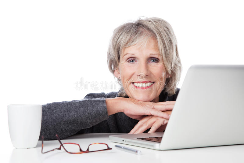 Smiling old woman behind laptop stock photography