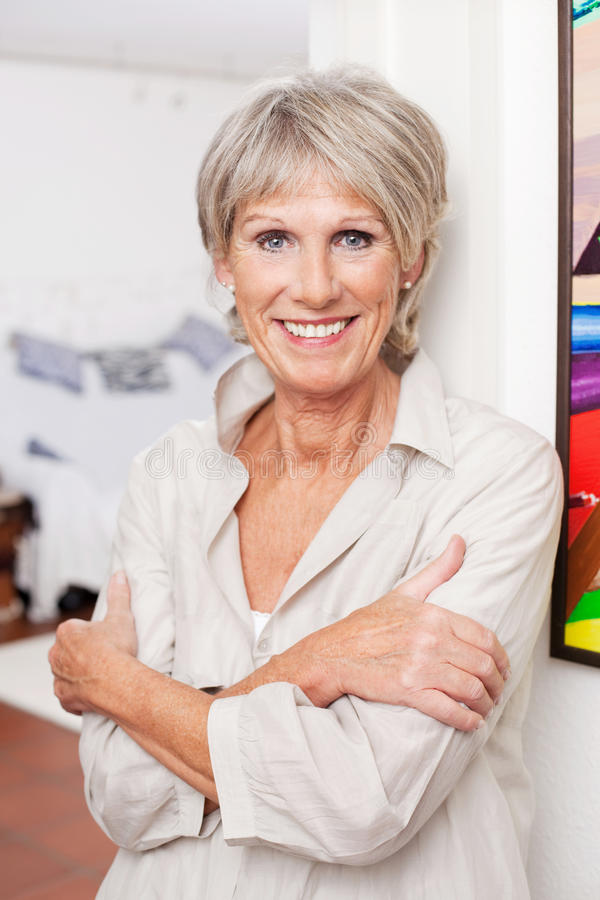 Smiling old woman. Posing with arms crossed stock images