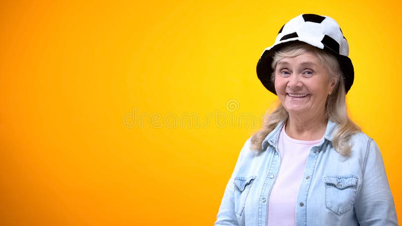 Smiling old woman wearing funny football hat, template for ad, sport betting royalty free stock photography