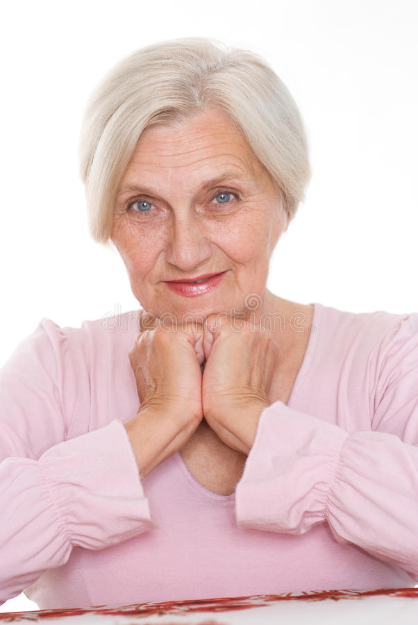 Smiling old women at the desk stock image