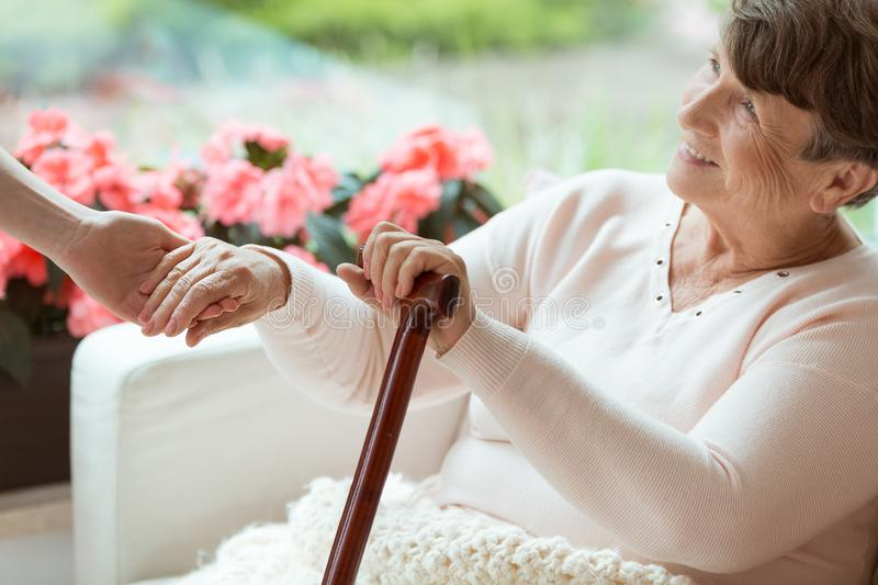 Smiling old woman. Smiling old women holding hands of assistant while sitting on white sofa with walking cane stock photography