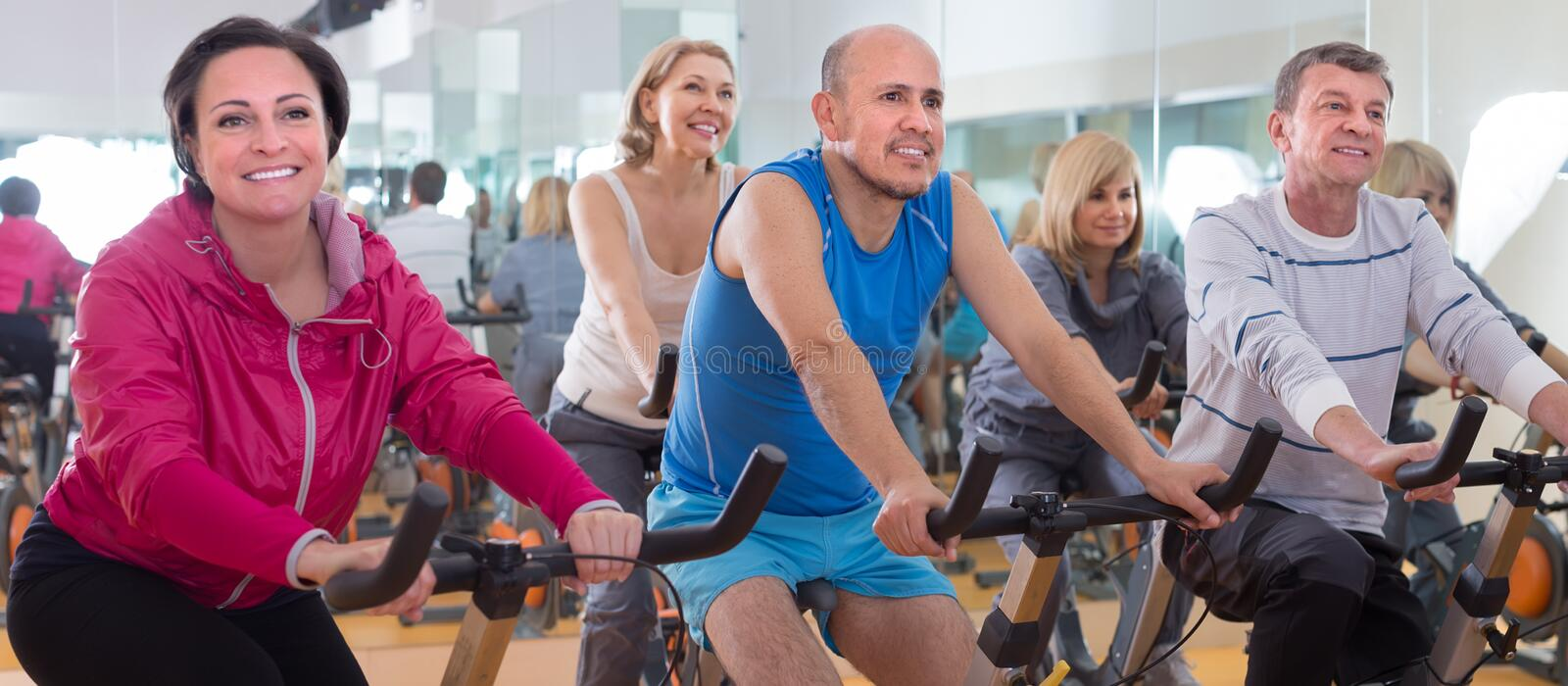 Older people do sports on exercise bikes royalty free stock images