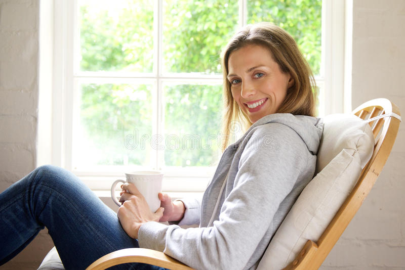 Smiling older woman relaxing at home with cup of tea stock photos
