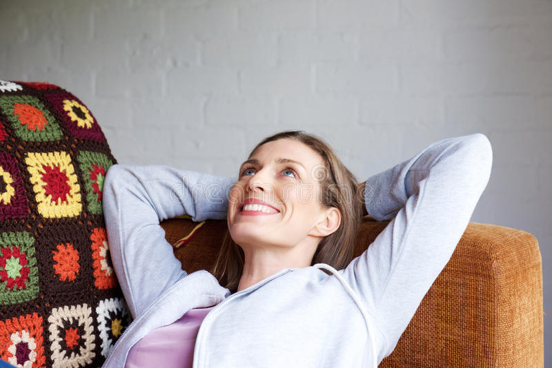 Smiling older woman relaxing at sofa home stock images