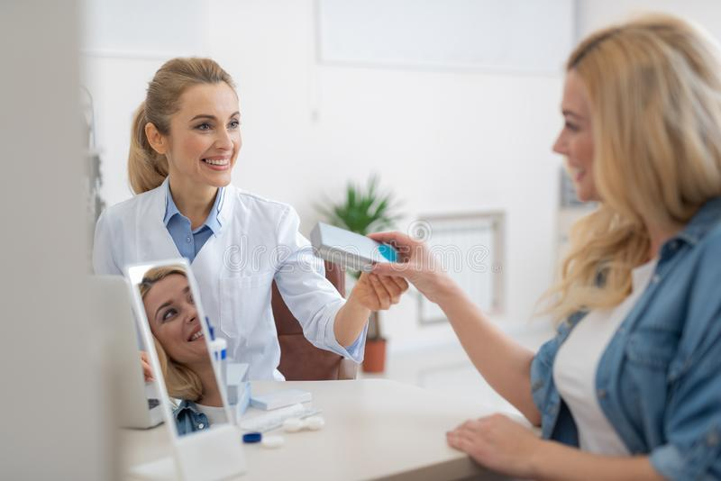 Friendly ophthalmologist in white lab coat prescribing contact lenses for blond lady. Smiling optician sitting at the table and giving silver packaging box with stock image