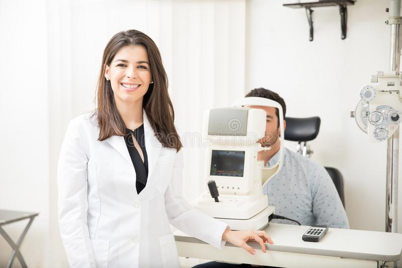 Smiling optometrist examining young patient on tonometer in ophthalmology clinic royalty free stock images