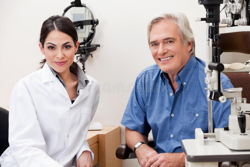 Smiling Optometrist With Her Patient. Confident female optometrist smiling with patient in her clinic royalty free stock photos