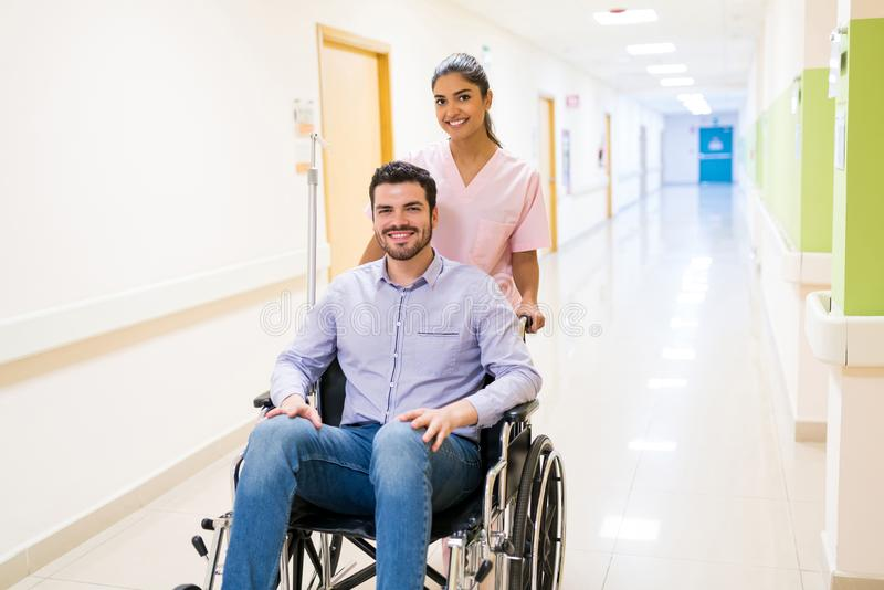 Female Healthcare Worker With Patient On Wheelchair At Hospital royalty free stock image