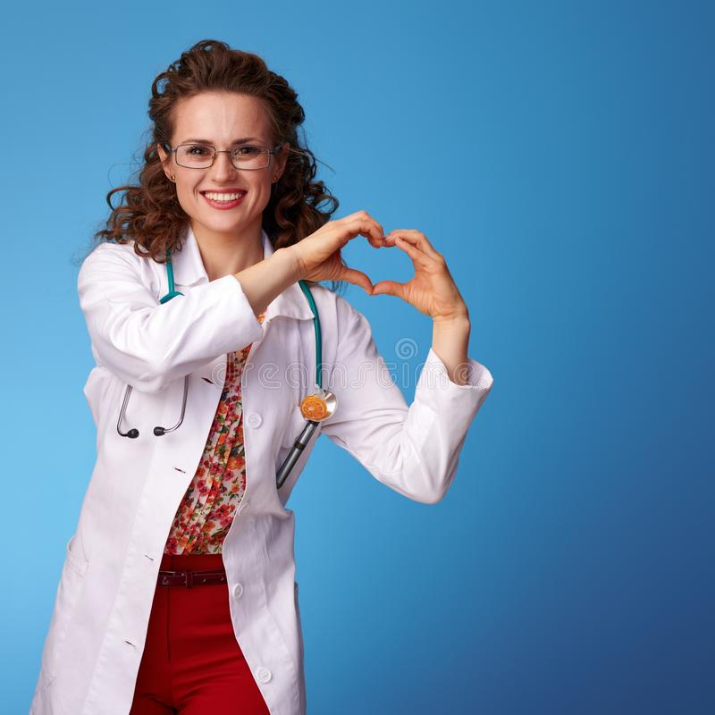 Smiling paediatrist doctor showing heart shaped hands on blue royalty free stock photo