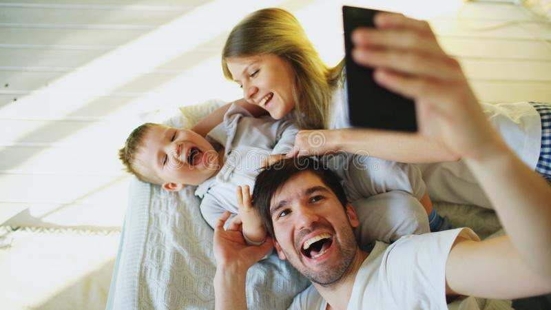 Smiling parents with baby taking selfie family photo on bed at home royalty free stock photos